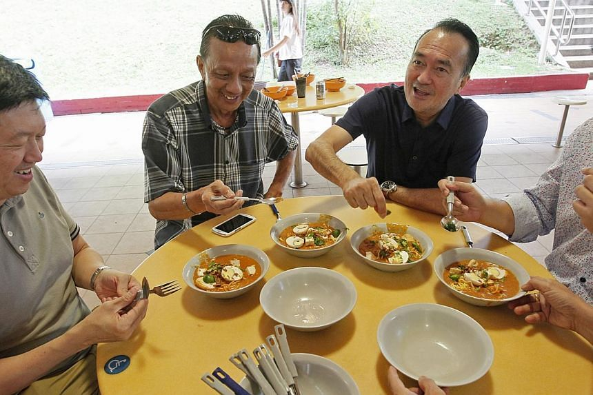(From left) Straits Times food critic Wong Ah Yoke, River Inn Group director Steven Yeong, Dennis Wee Group chairman Dennis Wee and Lianhe Zaobao zbNOW food correspondent Marcus Yeo tucking into mee rebus at one of the stalls visited yesterday. -- ST