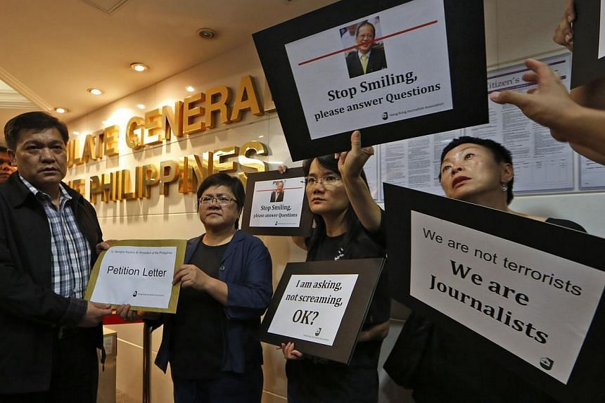 A representative of the Philippines Consulate (left) receives a letter of petition from members of Hong Kong Journalists Association during a protest at the Philippines Consulate in Hong Kong on Oct. 8, 2013. A journalist association is protesting th