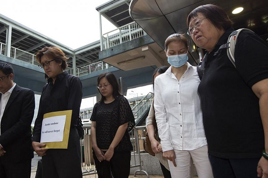 Mr Tse Chi Hang (second from left) and Ms Lee Mei Chun (right), family members of Hong Kong tour guide Masa Tse, who was killed during the 2010 Manila hostage crisis, and survivor Yik Siu Ling (second from right) observe a moment of silence outside t