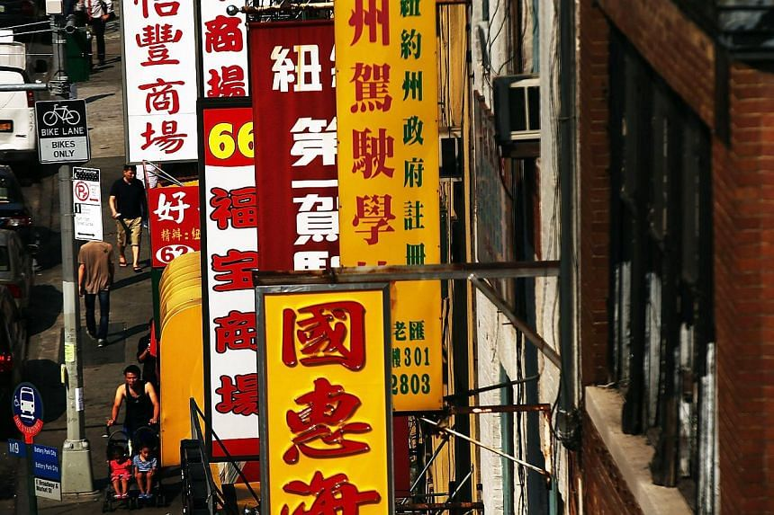 Signs hang on a Chinatown street as seen from the Manhattan Bridge on Aug 21, 2013 in New York City.Faced with a proliferation of luxury housing and chain stores, America's Chinatowns risk extinction as new immigrants are priced out of ci