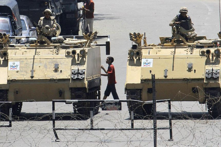 An Egyptian walking between armoured vehicles blocking Tahrir Square in Cairo, Egypt, on Aug 23, 2013.The United States said on Wednesday it would withhold deliveries of tanks, fighter aircraft, helicopters and missiles as well as cash assistan