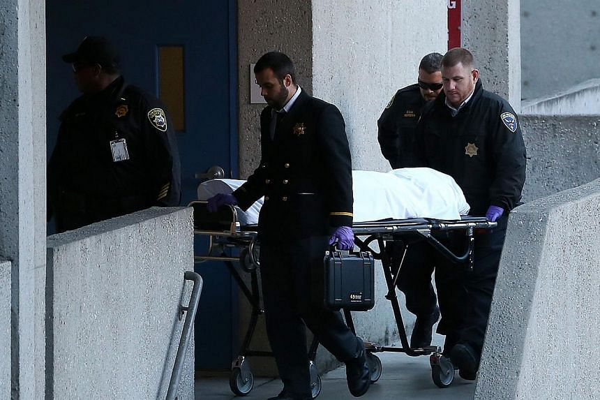 The medical examiner moves the body of 57-year-old Lynne Spalding on a gurney at San Francisco General Hospital on Oct 8, 2013 in San Francisco, California. -- PHOTO: AFP