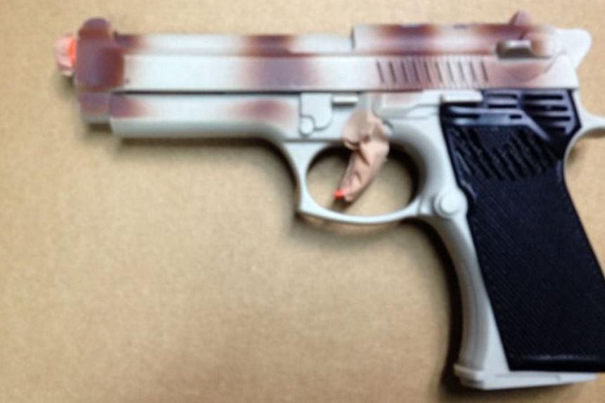 A Kazakhstan national was charged on Thursday with allegedly robbing a Japanese woman along Claymore Hill. Officers found a toy gun (above) on him. -- PHOTO: SINGAPORE POLICE FORCE