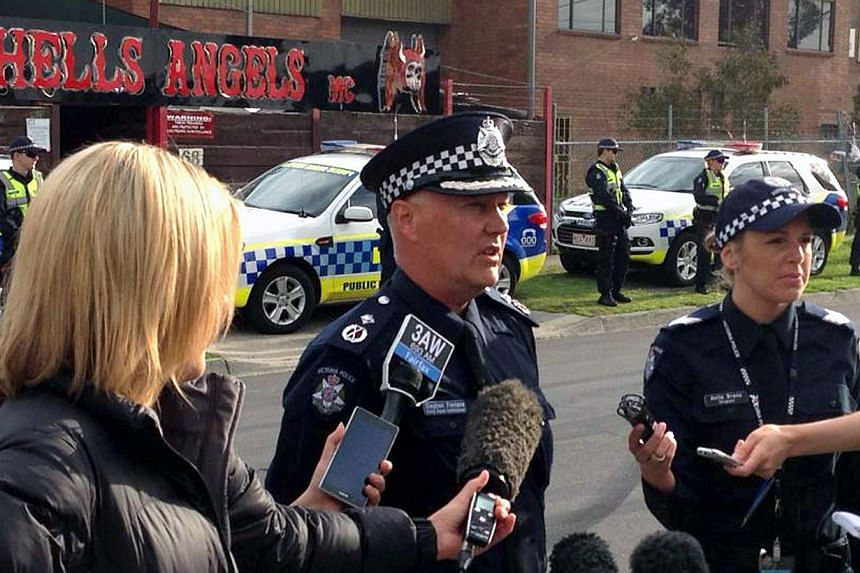 A handout photo taken and received on Thursday, Oct 10, 2013, shows Acting Deputy Commissioner Steve Fontana (centre) of Victoria Police speaking to the media outside a Hells Angels property in Melbourne.More than 700 Australian police swooped