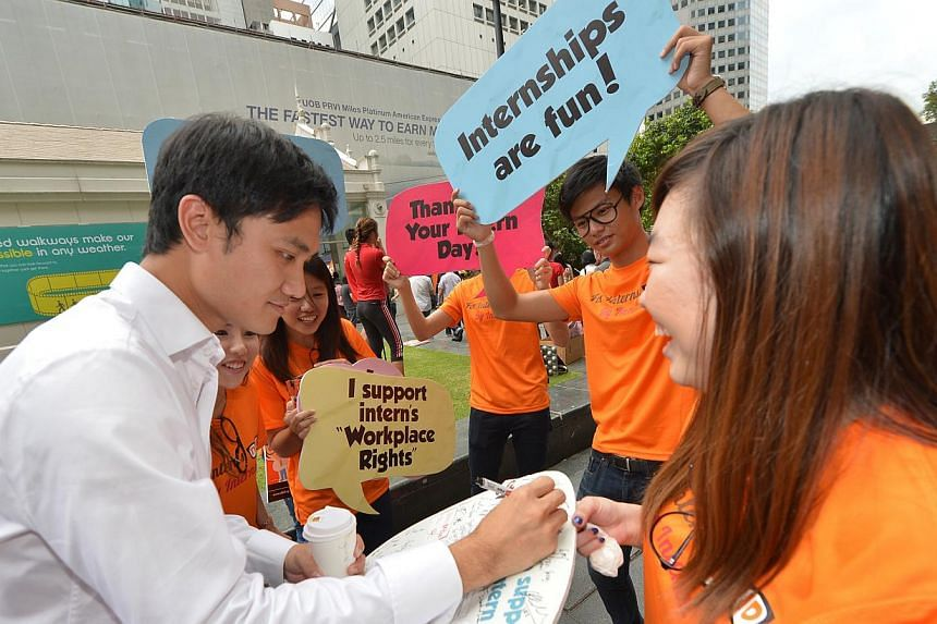 "Lawyer Nicholas Lauw, 32, stops by Raffles Place Square to pledge support for interns on his way back to work. Singapore's first ""Thank Your Intern Day"" took place at Raffles Place on Thursday with youth volunteers from nEbO - the junior members"