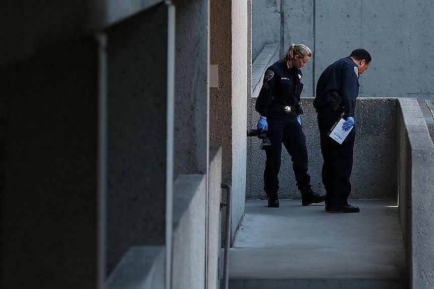 San Francisco police officers inspect an outdoor stairwell at San Francisco General Hospital on Oct 8, 2013 in San Francisco, California. -- PHOTO: AFP