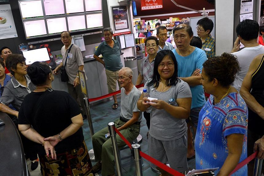 A queue at the Singapore Pools outlet in Toa Payoh Lorong 1, where Mr Poon Tong Wah (centre), 85, was given a chair by staff. He had been queuing for more than five hours. Betting services in many parts of Singapore were disrupted by the fire, which