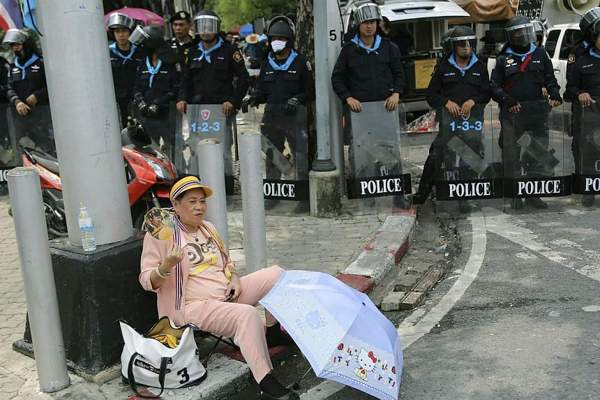 A Thai protester from the group The People's Army against Thaksin Regime sits in front of riot police during a demonstration outside the Government House Thursday, Oct. 10, 2013, in Bangkok, Thailand. -- PHOTO: AP