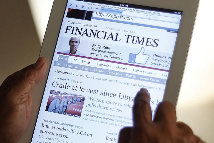 A man viewing the Financial Times on the iPad.The FT, which is owned by British company Pearson, saw web subscribers outstrip its print circulation for the first time last year. -- ST FILE PHOTO :TERENCE TAN
