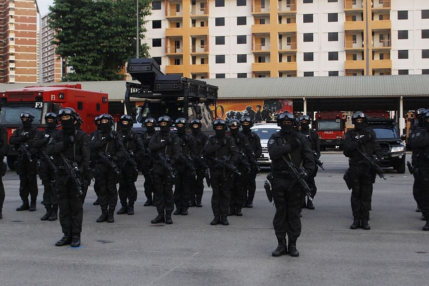 The Special Operations Command (SOC)Special Tactics and Rescue (STAR) Unit recite the Police Pledge, with the SOC vehicles in the background.The SOC of the Singapore Police Force celebrated its 60th anniversary with a parade at its Queens
