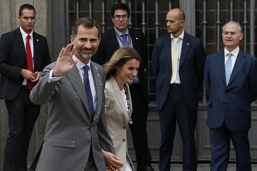Spain's Crown Prince Felipe waves as he walks with his wife,Princess Letizia, in Madrid on Oct 3, 2013.Crown Prince Felipe will take his ailing father's place saluting military officers at Spain's national day parade on Saturday, Oct 12,