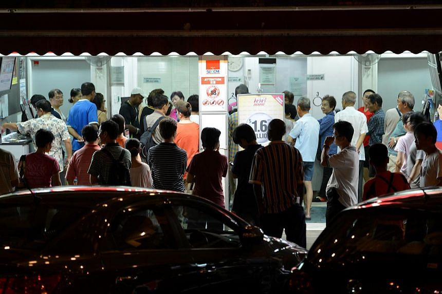 The queue outside the Singapore Pools outlet at Toa Payoh Lorong 1 at 7.50pm on Wednesday, Oct 9, 2013. -- ST PHOTO: CAROLINE CHIA