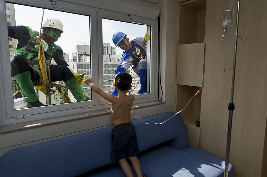 Window cleaners wearing superhero costumes greet a patient at a Children's Hospital, as part of the celebration of Children's Day in Sao Paulo, Brazil on Thursday, Oct 10, 2013. Children's Day is celebrated in Brazil on Saturday, Oct 12, 2013. -- PHO