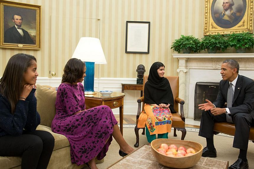 This official White House photo shows President Barack Obama, First Lady Michelle Obama, and their daughter Malia with Malala Yousafzai, the young Pakistani schoolgirl who was shot in the head by the Taleban a year ago, in the Oval Office, on Oct 11,