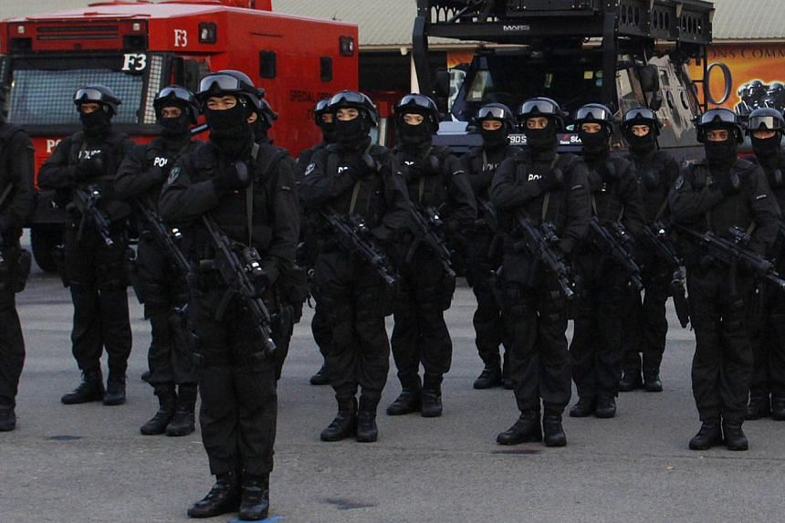 The Special Tactics and Rescue (Star) Unit reciting the Police Pledge, with the SOC vehicles in the background, during yesterday's parade at the command's Queensway base.