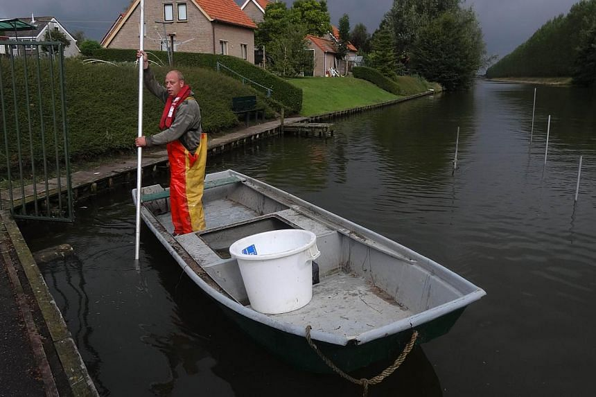 "Dutch fisherman Aart van der Waal brings a load of eels ashore on a small canal at Nieuwendijk on Sept 18, 2013 at the start of the ""Eels over the Dike"" project. -- FILE PHOTO: AFP"