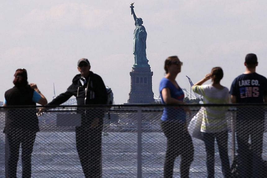 Tourists pause to view the Statue of Liberty from the deck of a Liberty Island ferry boat at Battery Park in New York in this file photo taken on Sep 30, 2013. US national parks and monuments including the Statue of Liberty and the Grand Canyon are t