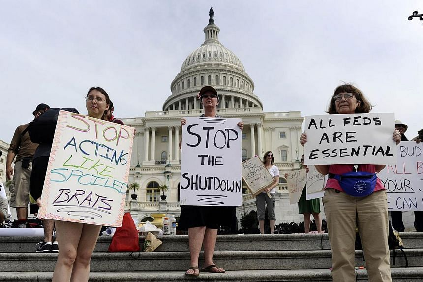 Protesters display placards during a demonstration in front of the United States (US) Capitol in Washington, DC, on Oct 3, 2013, urging congress to end the federal government shutdown. US economic growth could suffer a big hit in the fourth quarter i