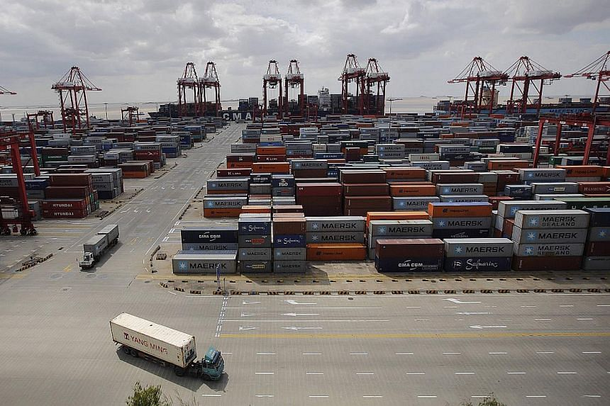 Container trucks drive past the container area at the Yangshan Deep Water Port, part of the newly announced Shanghai Free Trade Zone, south of Shanghai, on Sept 26, 2013. China's trade surplus narrowed to a disappointing US$15.2 billion (S$18.9 billi