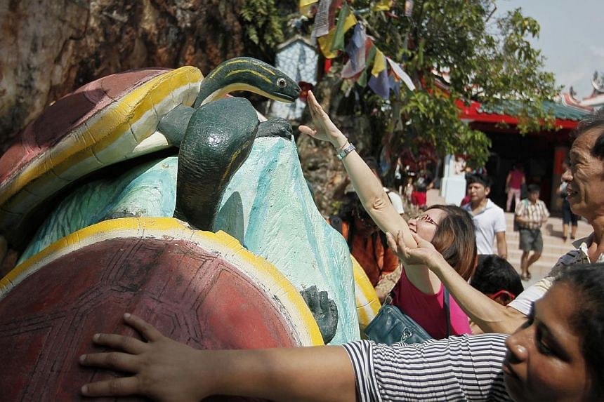 Ms Prasanna Reddy (foreground), reaches out to touch a sculpture of several turtles at Kusu Island's Da Bo Gong Temple on Oct 13, 2013. -- ST PHOTO: MARK CHEONG