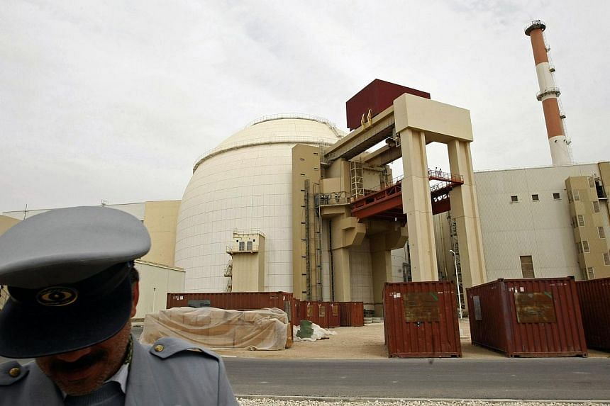 An Iranian security guard stands in front of the building housing the reactor of the Bushehr nuclear power plant in the Iranian port town of Bushehr, 1200 kilometres south of Tehran, on Feb 25, 2009. World powers will hold fresh talks wit