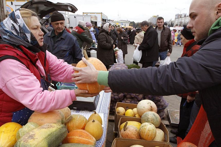 People buy vegetables at a street market during a fair in Minsk on Oct 5, 2013. Some European retailers are entering the market of ugly fruits and vegetables, positioning themselves as crusaders against food waste. -- PHOTO: REUTERS