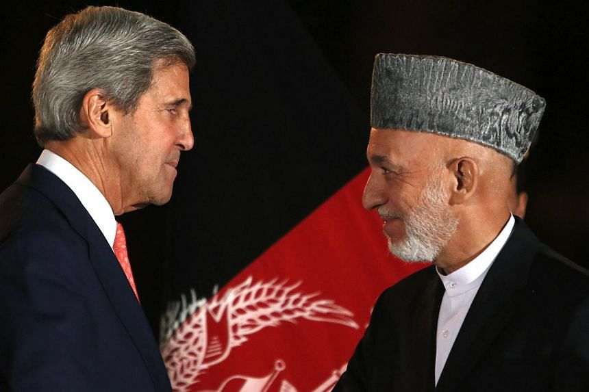 Afghanistan's President Hamid Karzai (right) talks with US Secretary of State John Kerry after a news conference in Kabul on Oct 12, 2013. Mr Karzai and Mr Kerry said on Saturday that talks on the future of US forces in Afghanistan were stuck on the