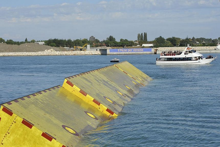"""Movable underwater panels emerge from the lagoon Saturday, Oct. 12, 2013, during the first official test of Venice movable barriers designed to rise from the seabed and prevent severe flooding in Venice, Italy. The project is named """"Moses,"""" after the"""