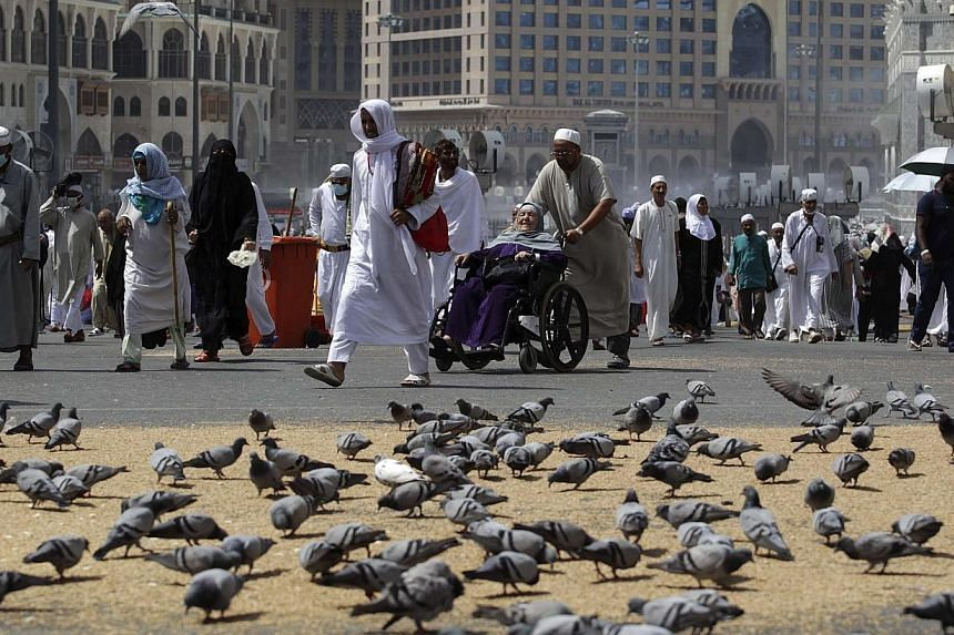 Muslim pilgrims walk past pigeons near the Grand Mosque in the holy city of Mecca, ahead of the annual haj pilgrimage onOct 12, 2013.-- PHOTO: REUTERS