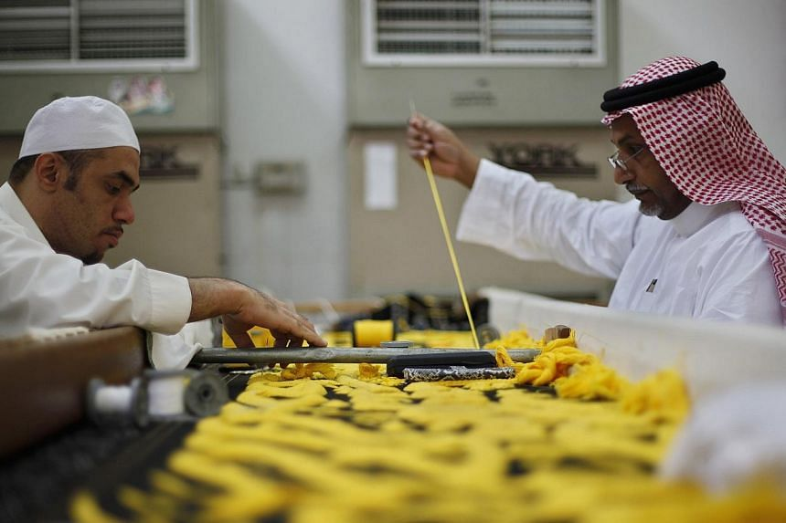 Workers embroider the Kiswa, a silk cloth covering the Holy Kaaba, in the holy city of Mecca, ahead of the annual haj pilgrimage on Oct 8, 2013.-- FILE PHOTO: REUTERS