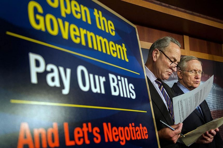 Democratic Senate Majority Leader Harry Reid (right) and US Senator Chuck Schumer stand near a placard during a press conference on Capitol Hill about the debt ceiling in Washington, DC, Oct 12, 2013.The Senate will hold a rare Sunday session a