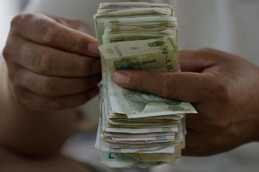 The Chinese yuan set a new peak against the US dollar on Monday, Oct 14, 2013, after the central bank guided the currency up through a record high guidance rate in the morning, as traders shrugged off negative export data. -- FILE PHOTO: REUTERS