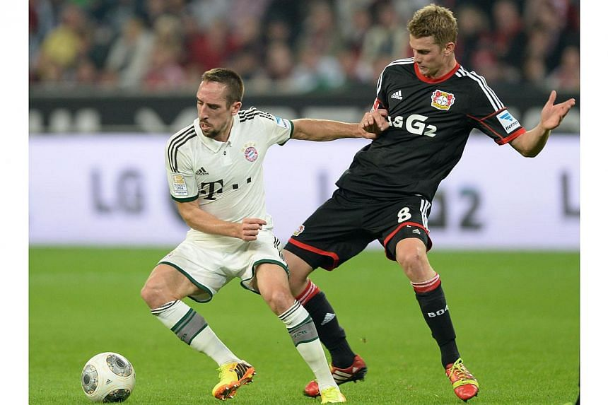 Leverkusen's midfielder Lars Bender (right) and Bayern Munich's French midfielder Franck Ribery vie for the ball during the German first division Bundesliga football match in the western German city of Leverkusen on Saturday, Oct 5, 2013.The Bu