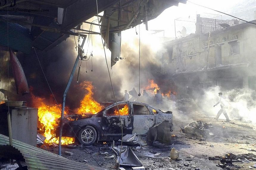 A handout picture released by the Syrian Observatory for Human Rightson Monday, Oct 14, 2013, shows vehicles burning following an explosion in the town of Darkoush, in Idlib province.A car bomb killed at least 20 people on Monday in the n