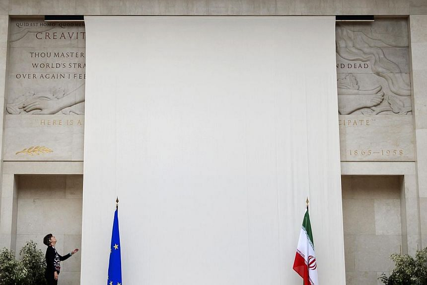 A woman looks at a sculpture of a naked man covered up by a curtain behind the European and Iranian flags on Monday, Oct 14, 2013, at the United Nations' Geneva offices.A relief carving of a naked man at the United Nations' Geneva headquarters