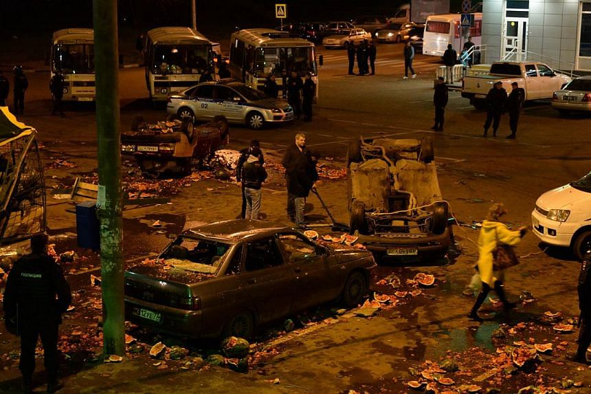 Police officers guard a vandalised street, the site of mass rioting in the southern Biryulyovo district of Moscow on Sunday, Oct 13, 2013.Moscow police were holding almost 400 people under arrest after the Russian capital was rocked by some of
