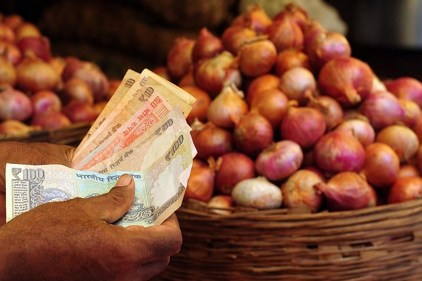An onion seller counts Indian rupee currency notes after a delivery at a market in Mumbai on Aug 22, 2013.A four-fold surge in the cost of onions helped push Indian inflation to a seven-month-high last month, fuelling expectations of another in
