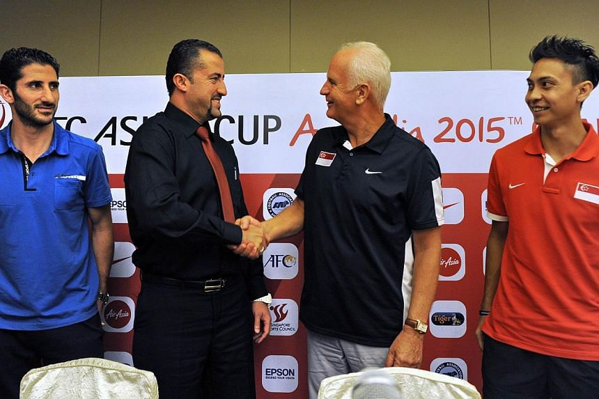 Singapore's football coach Bernd Stange (second from right) shakes hands with Syria's national team head coach Anas Makhlouf (second from left) while Syrian team captain Malki Sanhareb (left) and Singaporean team captain Shahril Ishak