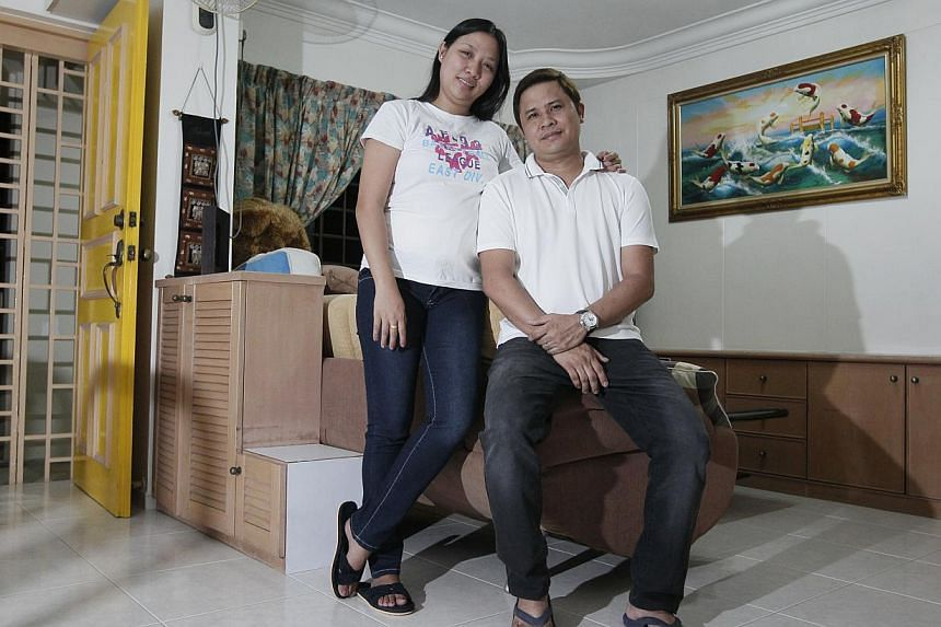 Filipino assistant retail manager Jovie Pascual, 36, with his wife Janette, 29, who works as a network administrator. He was downgraded to an S Pass holder in August as his pay did not meet the new salary criterion. -- ST PHOTO: MARK CHEONG