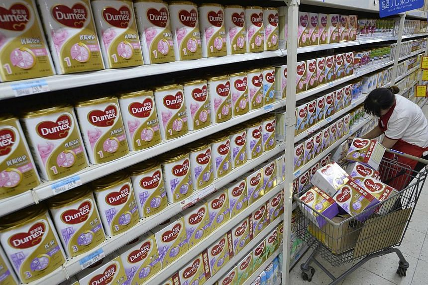 A sales assistant takes down Dumex milk powder products from shelves at a supermarket in Taiyuan, Shanxi province on Aug 5, 2013.Chinese authorities in the northern city of Tianjin have punished 13 medical workers for taking bribes from Danone