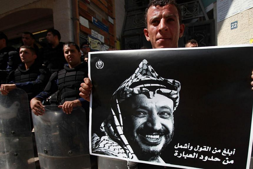 A Palestinian protestor, holding a poster of late Palestinian leader and founder of the Fatah movement Yasser Arafat, stands in front of Palestinian police standing guard outside the Qatari based Al-Jazeera Arabic news channel in the West Bank city o