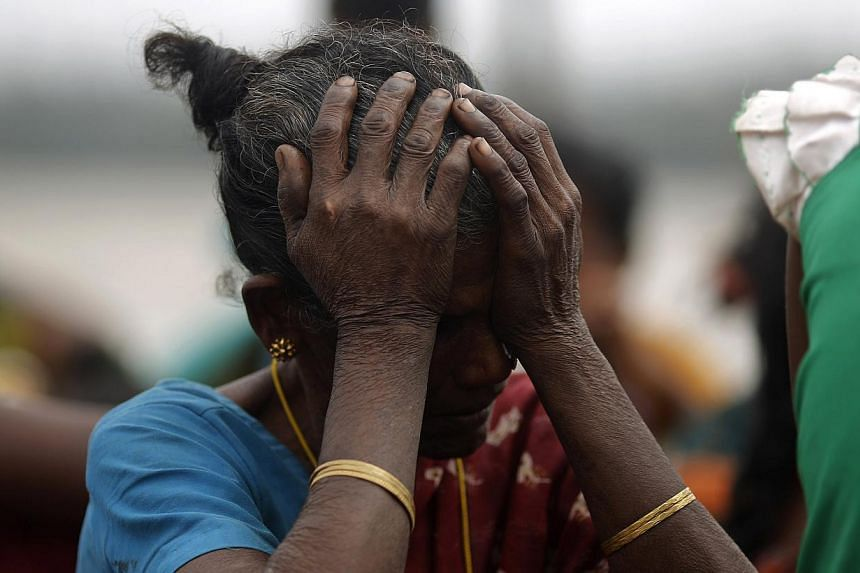A woman holds her head after Cyclone Phailin hit Sunapur village in Ganjam district in the eastern Indian state of Odisha on Oct 13, 2013.