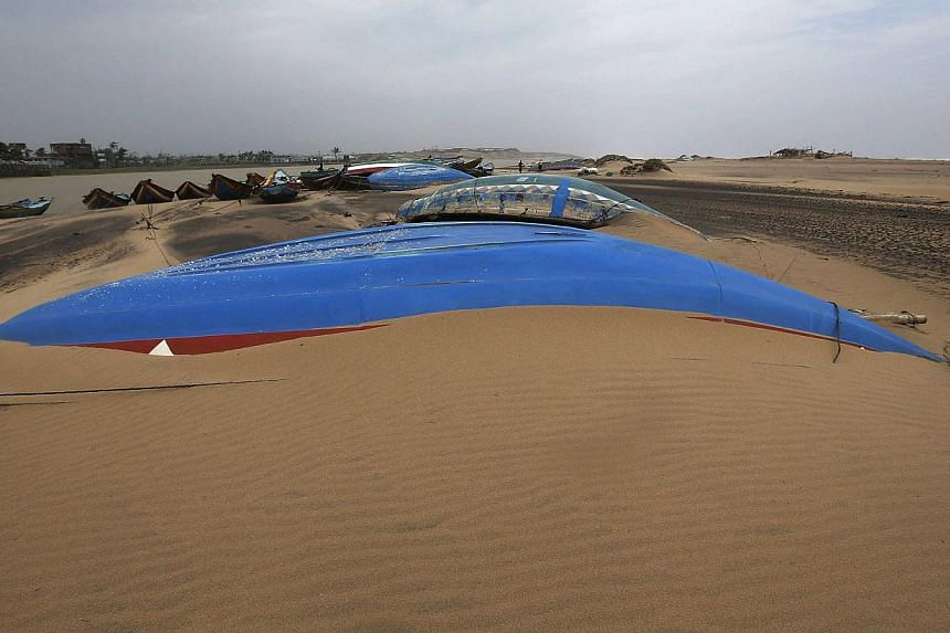 Boats are submerged in sand after Cyclone Phailin hit Gopalpur village in Ganjam district in the eastern Indian state of Odisha on Oct 13, 2013.