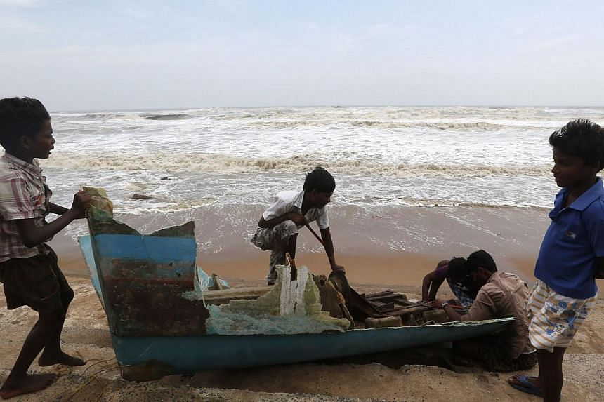 Boys watch as people remove usable parts from a damaged boat after Cyclone Phailin hit Gopalpur in Ganjam district in the eastern Indian state of Odisha on Oct 13, 2013.