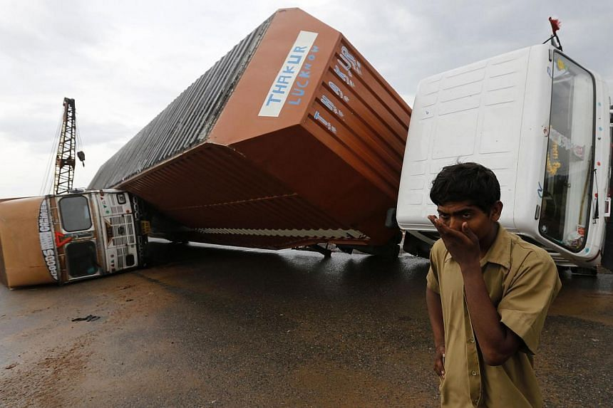 A man stands next to overturned trucks on a highway after Cyclone Phailin hit Girisola town in Ganjam district in the eastern Indian state of Odisha on Oct 13, 2013.