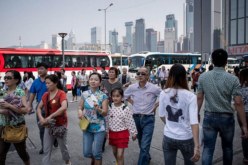 Chinese tourists visit a popular waterfront promenade in Hong Kong on Oct 2, 2013. Britain is to make it easier for Chinese nationals to obtain visas in an effort to boost business between the two countries, finance minister George Osborne has announ