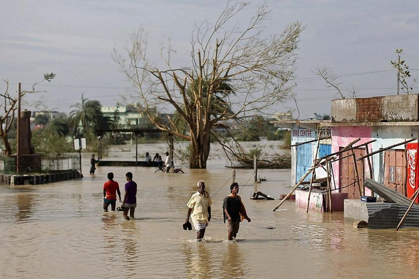 Residents wade through a flooded road after Cyclone Phailin hit Gopalpur in Ganjam district in the eastern Indian state of Odisha on Oct 13, 2013. India's strongest storm in 14 years left a trail of destruction along the country's east coast on Sunda