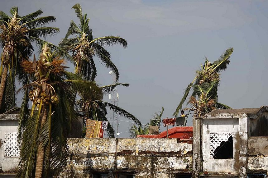 A boy stands on the roof of his home after Cyclone Phailin hit Brahmapur town in Ganjam district in the eastern Indian state of Odisha on Oct 13, 2013. Hundreds of thousands of people who fled India's strongest cyclone in 14 years returned to their d