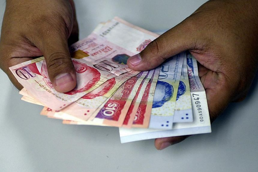 """Posed photo of hand holding Singapore dollar notes. The Monetary Authority of Singapore (MAS) has made no change to its monetary policy, maintaining its current stance of a """"modest and gradual appreciation"""" in the Singapore dollar. -- ST PHOTO: ABDUL"""