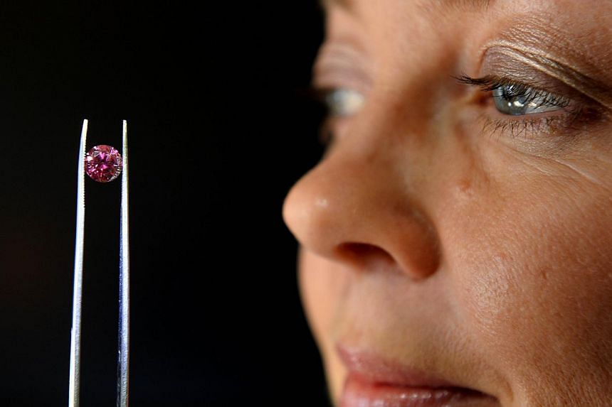 A file photo taken on May 17, 2013 shows Argyle Pink Diamonds manager Josephine Johnson inspecting the biggest 'red' diamond produced by mining giant Rio Tinto's Australian mine, in Sydney. -- FILE PHOTO: AFP